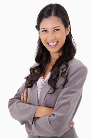 Smiling businesswoman with arms folded against a white background Stock Photo