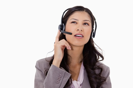 caller: Businesswoman listening to caller with headset against a white background