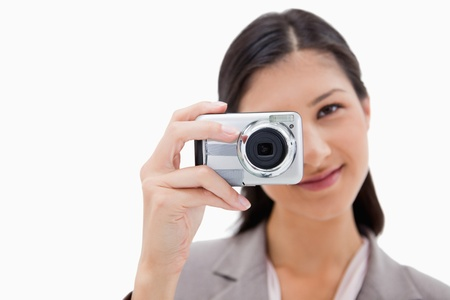 Businesswoman taking a picture against a white background photo