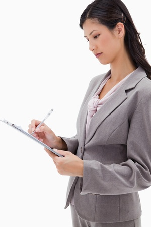 Side view of businesswoman with clipboard against a white background photo