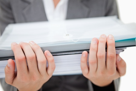 Pile of paperwork being held by female hands against a white background photo