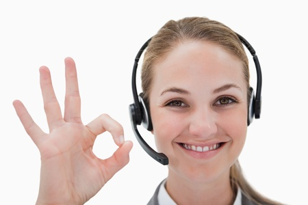 Smiling call center agent approving against a white background photo
