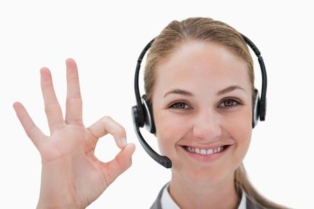 call center agent: Sorridente operatore di call center che approva contro uno sfondo bianco Archivio Fotografico