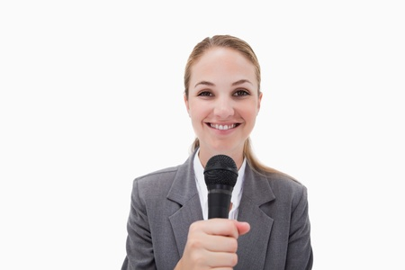 Smiling woman with microphone against a white background Stock Photo - 11687321
