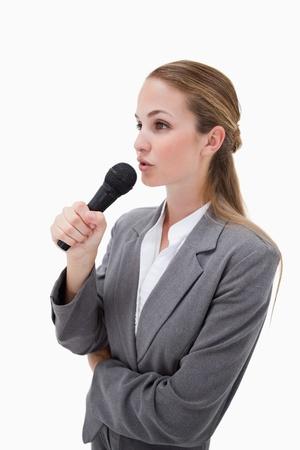 Zijaanzicht van vrouw met microfoon tegen een witte achtergrond