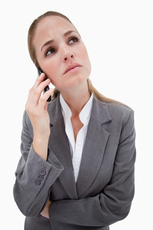Sad bank employee on her cellphone against a white background photo