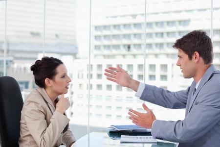 dos personas hablando: Equipo de un asunto serio de negociaci�n en una sala de reuniones Foto de archivo