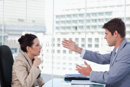 two people talking: Serious business team negotiating in a meeting room Stock Photo