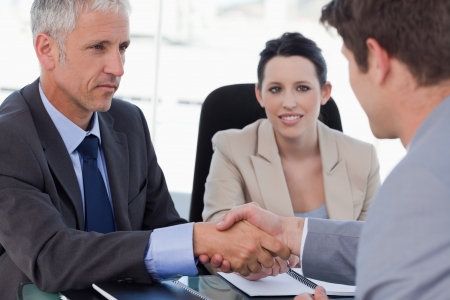 concluding: Business team concluding an agreement with a client in a meeting room