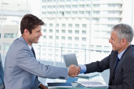 Businessmen shaking hands in an office photo