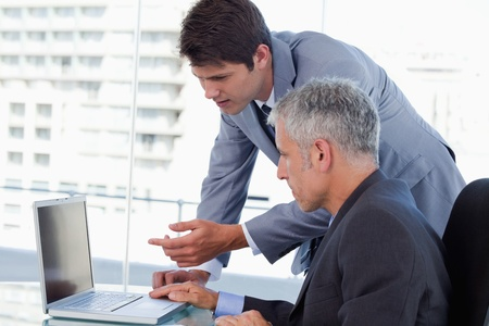 Side view of businessmen working with a laptop in an office Stock Photo - 18681147