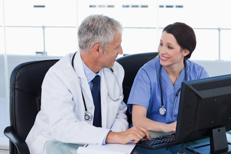 Medical team working with a computer in an office Stock Photo - 13616433