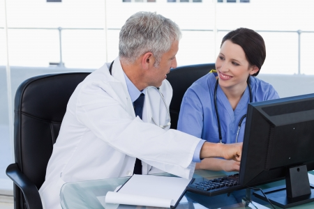Smiling medical team working with a computer in an office Stock Photo - 13616453