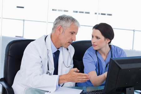 Serious medical team working with a computer in an office Stock Photo - 13615933