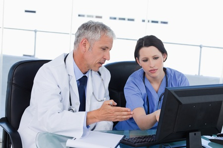 medical physician: Professional medical team working with a computer in an office