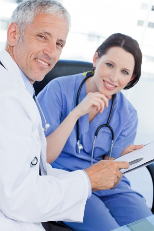 Portrait of a smiling medical team looking a document in an office Stock Photo - 13600347