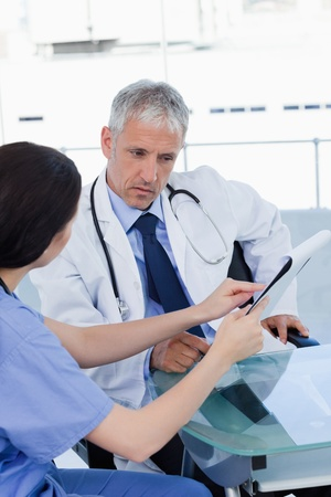Portrait of a seus medical team looking a document in an office Stock Photo - 13616378