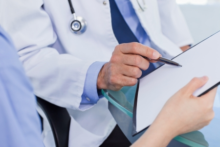 medical report: Close up of a medical team looking a document in an office