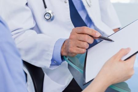 equipe medica: Primo piano di un gruppo di medici in cerca di un documento in un ufficio