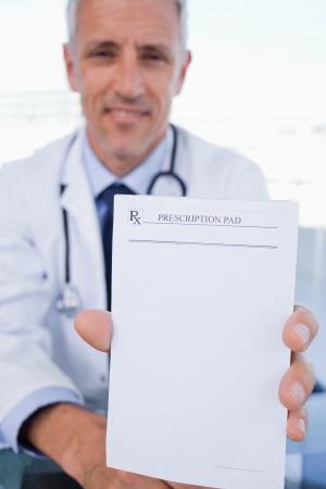 recetas medicas: Retrato de un doctor de sexo masculino que muestra una hoja de prescripci�n en blanco en su oficina
