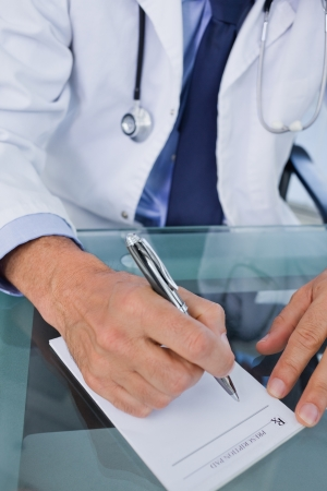 Portrait of a doctor writing a prescription on a desk photo