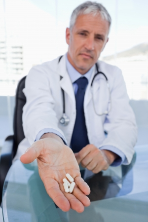 Portrait of a doctor showing pills in his office photo