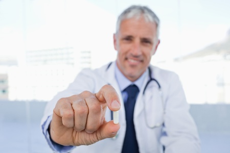 Doctor showing a pill in his office photo