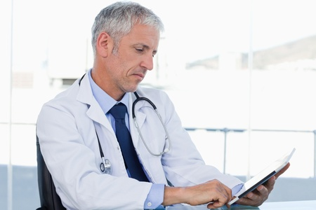 touchpad: Doctor working with a tablet computer in his office Stock Photo