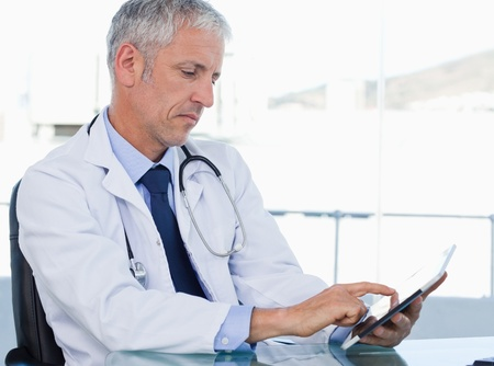 Serious doctor working with a tablet computer in his office photo
