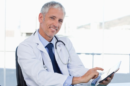 healthcare office: Smiling doctor working with a tablet computer in his office