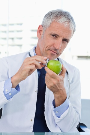 Portrait of a doctor putting his stethoscope on an apple in his office photo