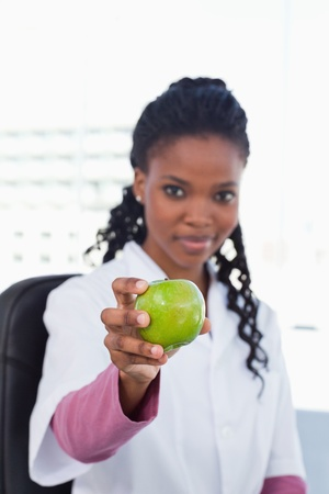 Portrait of a female doctor showing an apple in her office photo