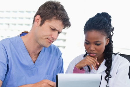 Doctors looking at a document in an office Stock Photo - 13616495