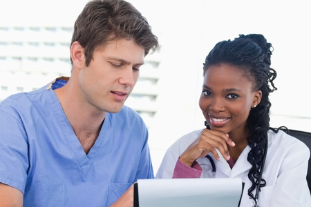 Smiling doctors looking at a document in an office Stock Photo - 13616517