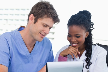 Happy doctors looking at a document in an office Stock Photo - 13600231