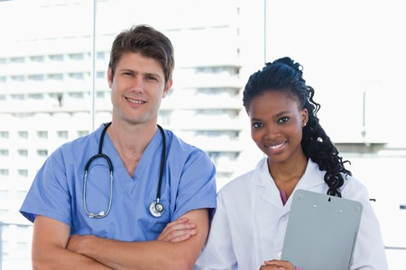 Happy doctors posing in an office Stock Photo - 13616369