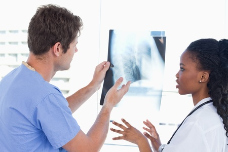Young doctors looking at a of X-ray in an office Stock Photo - 13616439