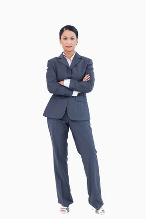 Businesswoman standing with arms folded against a white background Stock Photo - 13601332