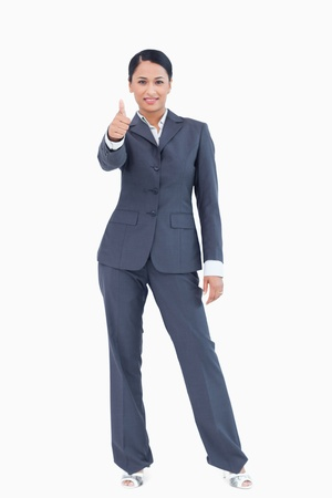 Standing businesswoman giving thumb up against a white background photo