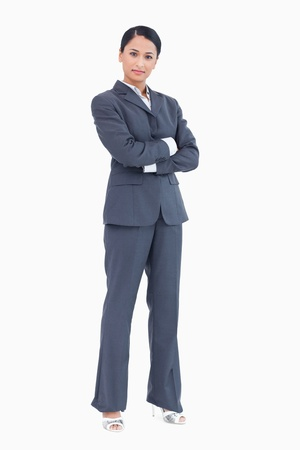 Confident standing businesswoman with arms folded against a white background Stock Photo - 13601331