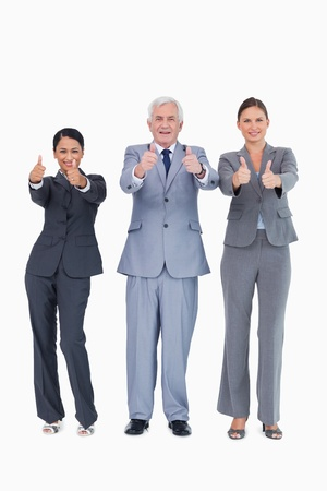 Three smiling businesspeople giving thumbs up against a white background photo