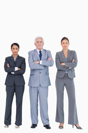 Three businesspeople with arms folded against a white background photo