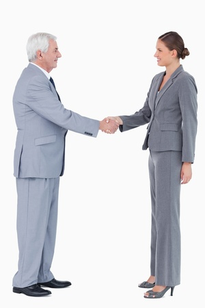 Side view of smiling businesspartner shaking hands against a white background photo
