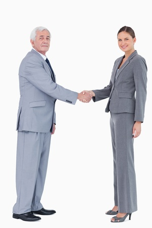 Businessman and woman shaking hands against a white background photo