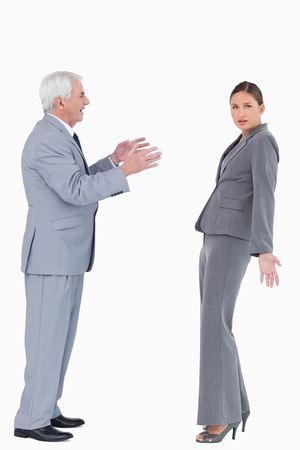 Businesswoman getting accused by colleague against a white background photo