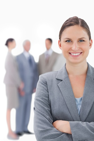Smiling businesswoman with her colleagues behind her against a white background photo