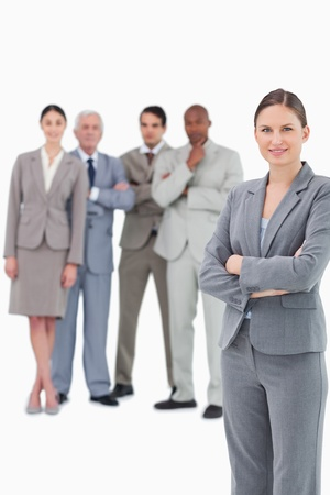 Saleswoman with arms folded and her team behind her against a white background photo