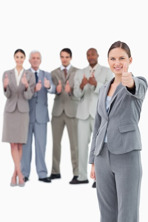 Saleswoman with thumb up and her team behind her against a white background photo