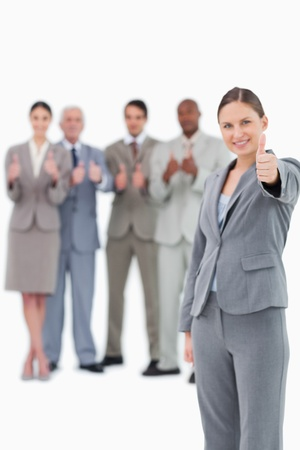 Tradeswoman with thumb up and colleagues behind her against a white background Stock Photo - 13606714