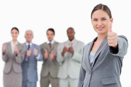 Businesswoman with thumb up and colleagues behind her against a white background photo